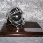 Hjelm i metal på træplade. Mål H 100 x B 180 mm  Dkr : 350,00